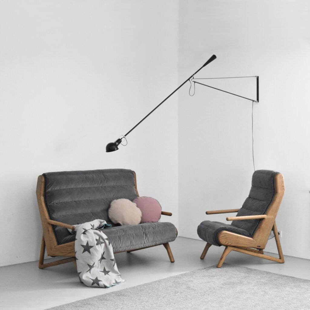 dębowy fotel Cameleon z pikowaną odsuwaną tapicerką w minimalistycznym wnętrzu z lampą Flos